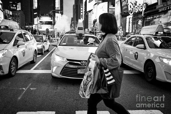 Evening Art Print featuring the photograph woman crossing crosswalk in front of yellow cabs in the evening in Times Square New York City USA by Joe Fox