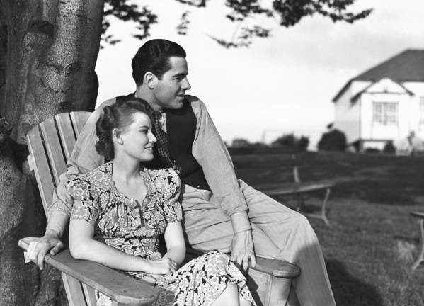 30-34 Years Art Print featuring the photograph Couple Relaxing On Deckchair In Garden, (b&w) by George Marks