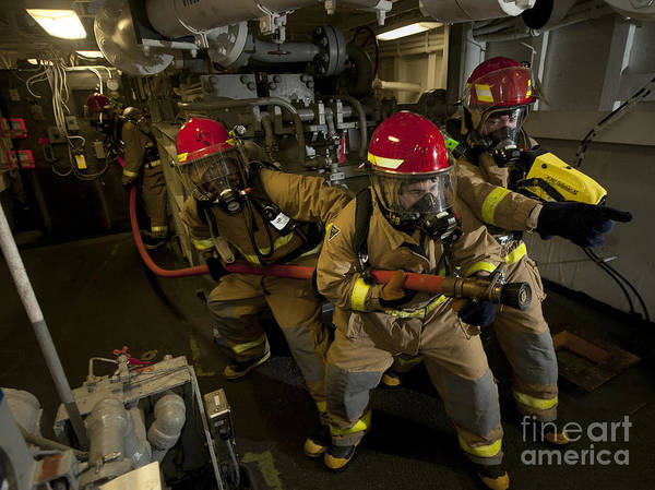 Warship Art Print featuring the photograph Firemen Combat A Simulated Fire Aboard by Stocktrek Images