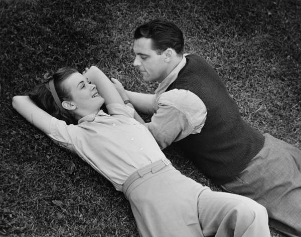 30-34 Years Art Print featuring the photograph Romantic Couple Lying On Grass, (b&w), Elevated View by George Marks