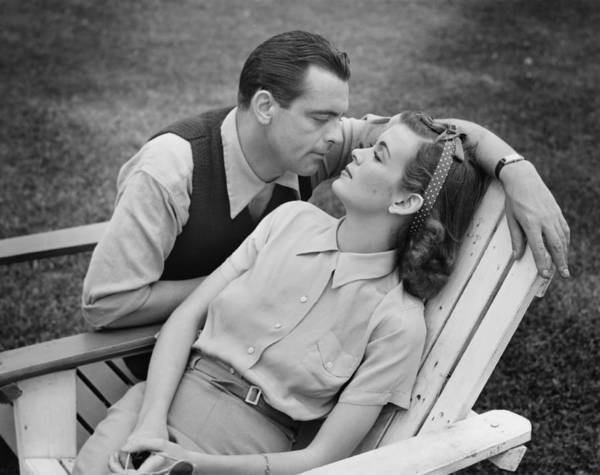 30-34 Years Art Print featuring the photograph Romantic Couple Relaxing On Deckchair, (b&w) by George Marks