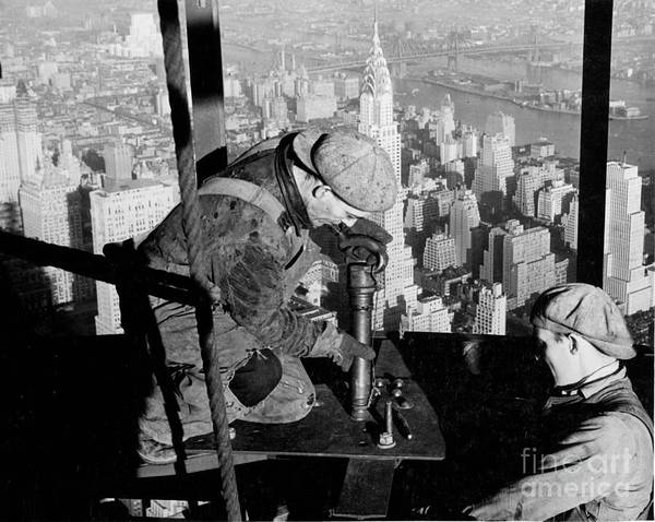 Riveters; Riveting; Male; Work; Labour; Workers; Working; Labourers; Construction; Building; History; Historical; Landmark; Skyscraper; High-rise; Empire State Building; 1930s; 30s; Thirties; Us; Usa; America; American; United States; High; Challenge; Risk; Danger; Courage; Bravery; Heights; Achievement; Scale; Teamwork; Chrysler Building; Aerial View; New York; Manhattan; Architecture; Urban; City; Cityscape; Dramatic; Builder; Builders; Scenic; Concentration; Black And White Photograph; B/w Photo; Photography Art Print featuring the photograph Riveters On The Empire State Building by LW Hine