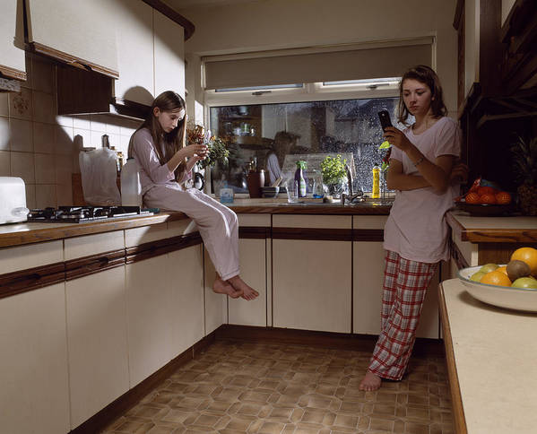 Two Sisters (11-14) Using Mobile Phones In Kitchen, Dusk Art Print