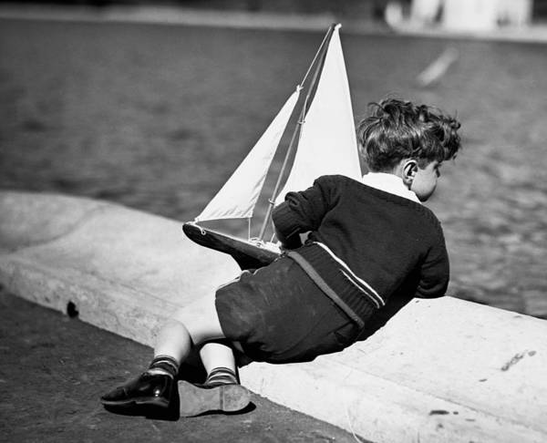 Child Art Print featuring the photograph Boy Playing With Toy Sailboat by George Marks