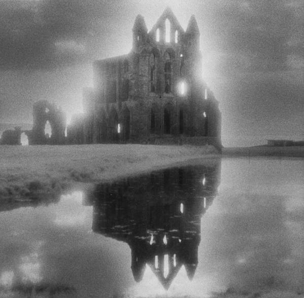 Eerie; Atmospheric; Spooky; Haunted; Haunting; Dramatic; Striking; Misty; Hazy; Lake; Reflection; English; Architecture; Exterior; Ruin; Ruins Art Print featuring the photograph Whitby Abbey by Simon Marsden
