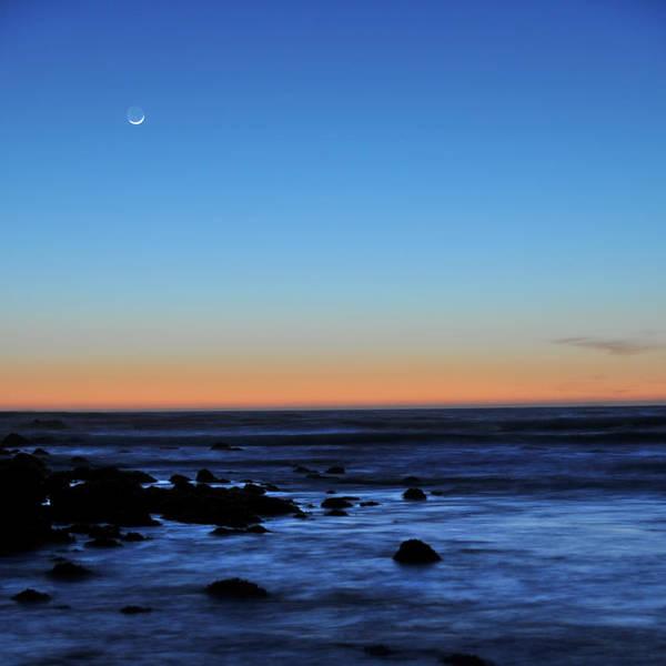Moon Art Print featuring the photograph Crescent Moon Above A Rocky Shore by Scott Lenhart