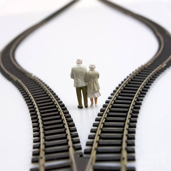 Contemplates Art Print featuring the photograph Figurines Between Two Tracks Leading Into Different Directions Symbolic Image For Making Decisions. by Bernard Jaubert