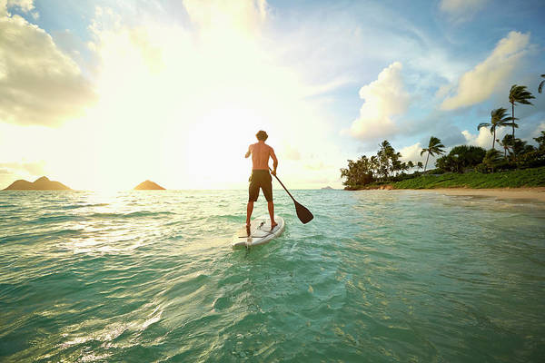 Tranquility Art Print featuring the photograph Caucasian Man On Paddle Board In Ocean by Colin Anderson Productions Pty Ltd
