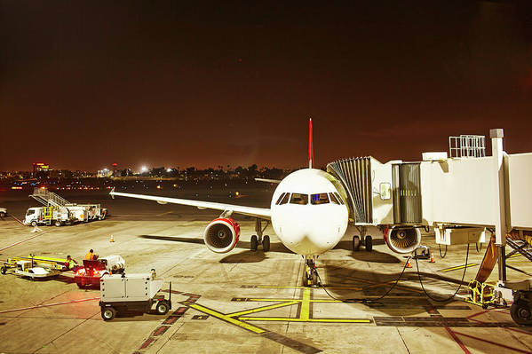 Passenger Boarding Bridge Art Print featuring the photograph Airplane Parked At Jetway by Ballyscanlon