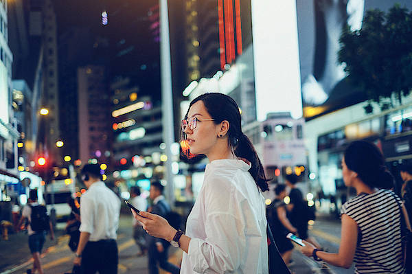 Financial Building Art Print featuring the photograph Beautiful Asian woman using mobile phone while crossing road in busy downtown city street at night by D3sign
