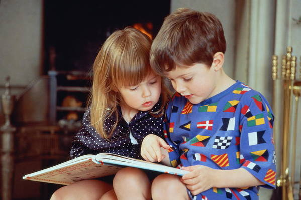4-5 Years Art Print featuring the photograph Boy(4-5)and girl(2-3)sat by fire in pyjamas reading book together by Bob Thomas
