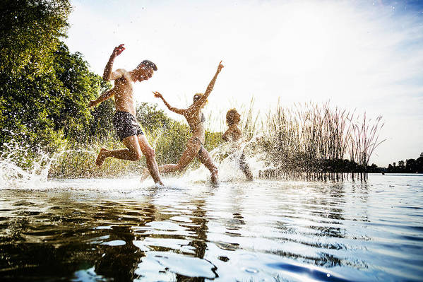 Young Men Art Print featuring the photograph Friends Splashing In Water At Lake Together by TommL