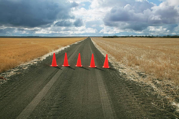 Orange Color Art Print featuring the photograph Safety Cones Lined Up Across A Rural by Benjamin Rondel / Design Pics