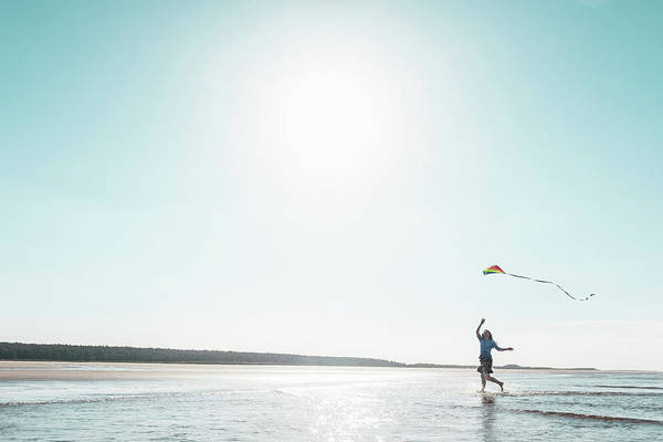 Three Quarter Length Art Print featuring the photograph Woman Flying Kite On Beach by Dan Brownsword