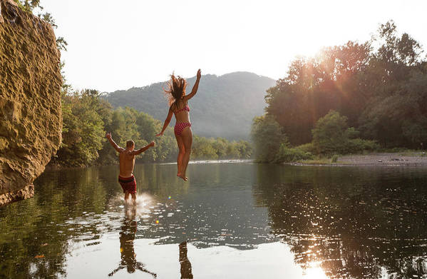 Young Men Art Print featuring the photograph Young Couple Jumping Into River by Zave Smith