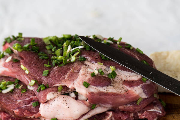 Background Art Print featuring the photograph Pork meat with green garlik and knife by Adrian Bud
