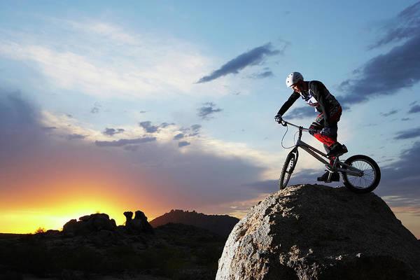 Sports Helmet Art Print featuring the photograph Bike Rider Balancing On Rock Boulder by Thomas Northcut