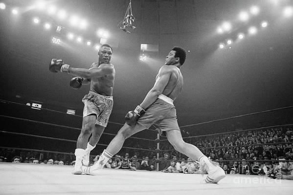 Joe Frazier Art Print featuring the photograph Boxer Ali Dodging A Punch From Frazier by Bettmann