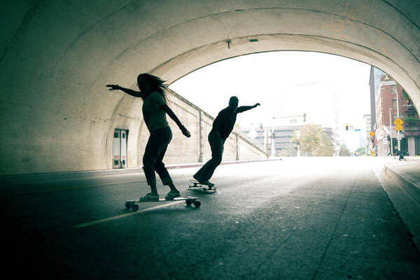 Mature Adult Art Print featuring the photograph Couple Skateboarding Through Tunnel by Ian Logan