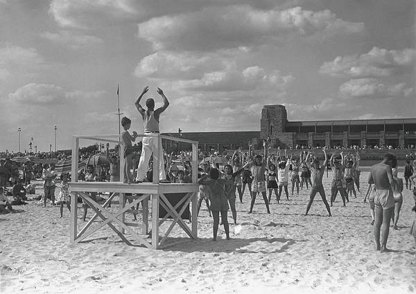 Human Arm Art Print featuring the photograph Group Of People Exercising On Beach, B&w by George Marks