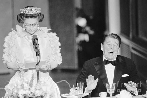 Following Art Print featuring the photograph President Reagan Laughing At Queens by Bettmann