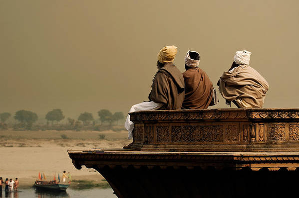 Water's Edge Art Print featuring the photograph Three Sadhus Meditating By The Yamuna by Globalstock