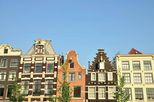 In A Row Art Print featuring the photograph Typical Canal Houses, Amsterdam, The by Gorazdbertalanic