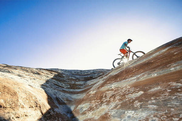 People Art Print featuring the photograph A man riding a mountain bike on an extreme sandstone ledge by Robb Reece