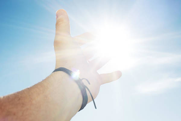 People Art Print featuring the photograph Mans hand reaching for sun by Hup