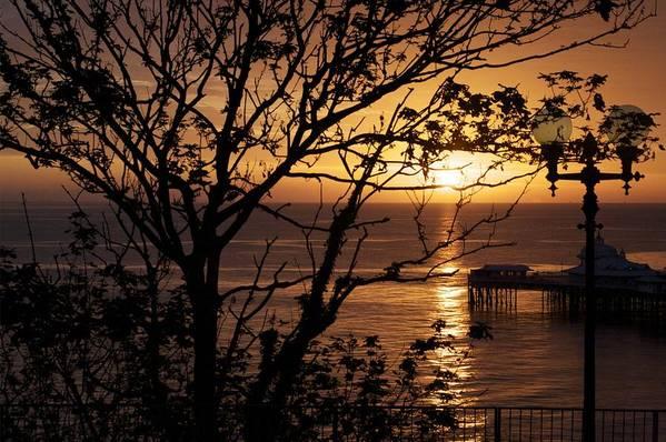 Sun Art Print featuring the photograph Sunrise over Llandudno pier by Christopher Rowlands