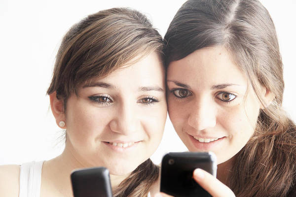 People Art Print featuring the photograph Teenage girls using cell phones by Sigrid Gombert