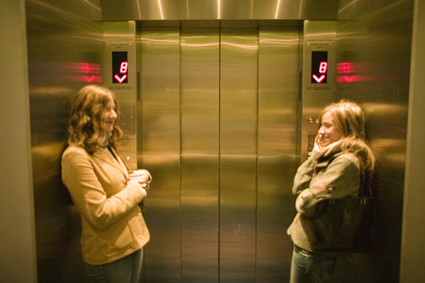 Three Quarter Length Art Print featuring the photograph Two young women waiting in elevator by Photodisc