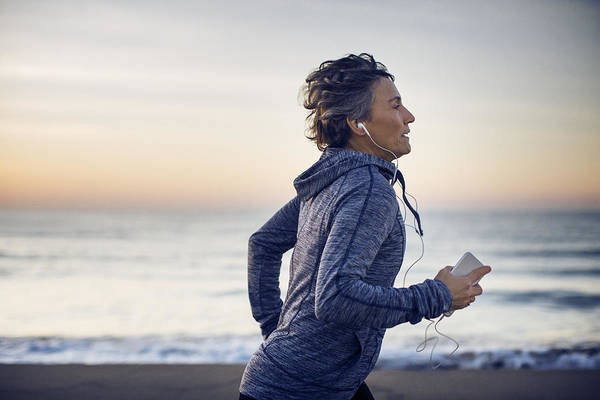 Tranquility Art Print featuring the photograph Woman jogging while listening music at beach against sky by Cavan Images