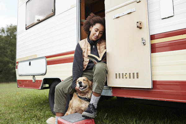 Pets Art Print featuring the photograph Woman with dog reading book in motor van by Klaus Vedfelt