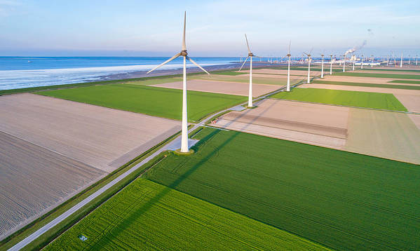 Wind Art Print featuring the photograph Wind turbines lined up along coast towards industrial area by Daniel Bosma