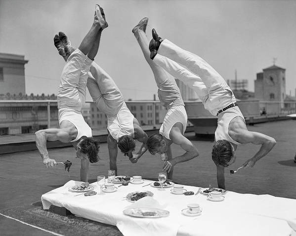 People Art Print featuring the photograph Acrobats Eat While Doing Handstands by Bettmann