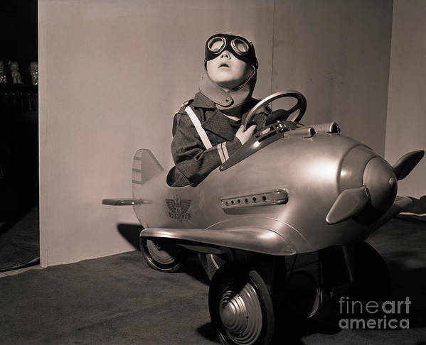 Child Art Print featuring the photograph Boy In Aviator Suit Sitting In Toy Plane by Bettmann