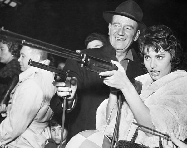 Expertise Art Print featuring the photograph John Wayne And Sophia Loren Gun Play by Bettmann