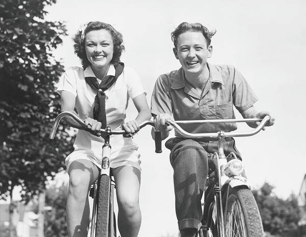 Young Men Art Print featuring the photograph Man And Woman Riding Bikes, B&w, Low by George Marks