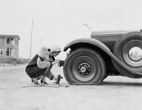 People Art Print featuring the photograph Woman Changing Flat Tire On Car by H. Armstrong Roberts