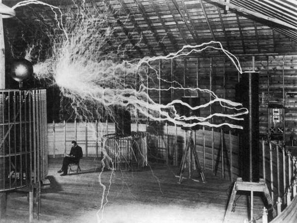 Physicist Art Print featuring the photograph Bolts of electricity discharging in the lab of Nikola Tesla. by John Parrot/Stocktrek Images