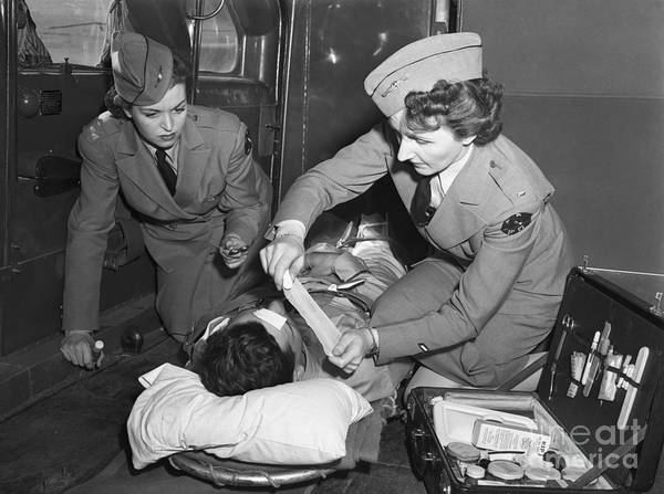 Ambulance Art Print featuring the photograph Military Nurses Treating Wounded Soldier by Bettmann