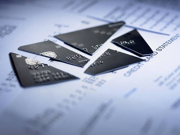 Debt Art Print featuring the photograph Close up of cut pieces of credit card by Adam Gault