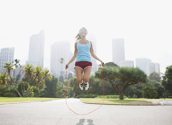 People Art Print featuring the photograph Woman skipping rope in park by Tom Merton