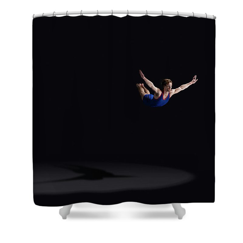 Expertise Shower Curtain featuring the photograph Male Gymnast Soaring Through The Air by Mike Harrington