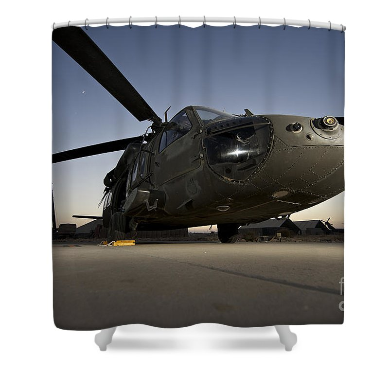 Isaf Shower Curtain featuring the photograph A Uh-60l Blackhawk Parked On Its Pad by Terry Moore