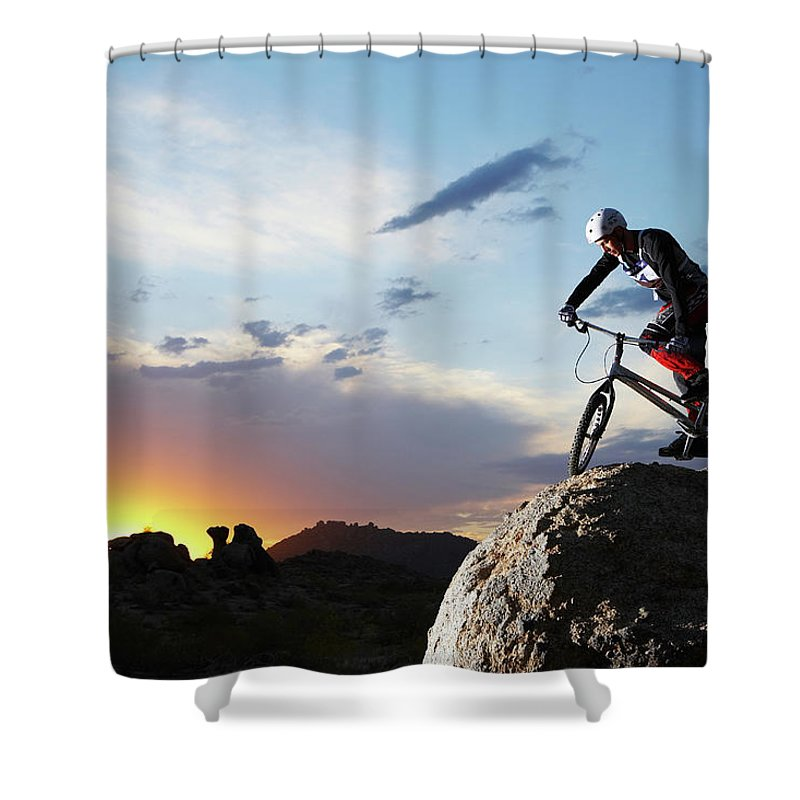 Sports Helmet Shower Curtain featuring the photograph Bike Rider Balancing On Rock Boulder by Thomas Northcut