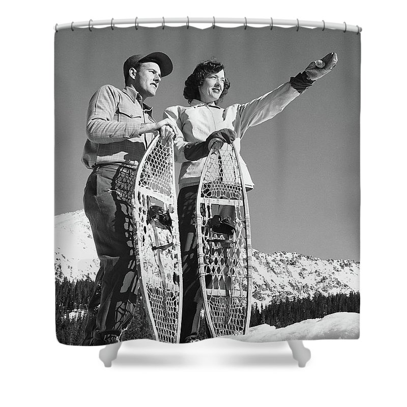 Heterosexual Couple Shower Curtain featuring the photograph Couple Holding Snowshoes, Woman Pointing by Stockbyte
