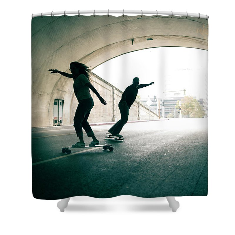 Mature Adult Shower Curtain featuring the photograph Couple Skateboarding Through Tunnel by Ian Logan