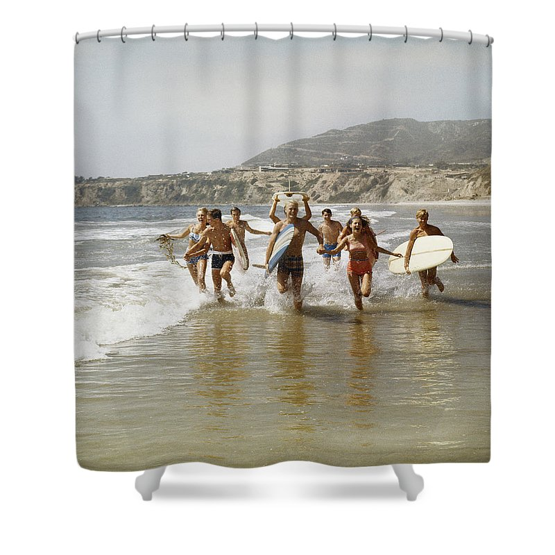 Young Men Shower Curtain featuring the photograph Group Of Surfers Running In Water With by Tom Kelley Archive